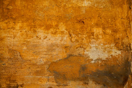 The rough surface of the rough stone yellow. Background in grunge style. texture of old wall with peeling paint. Abstract background yellow