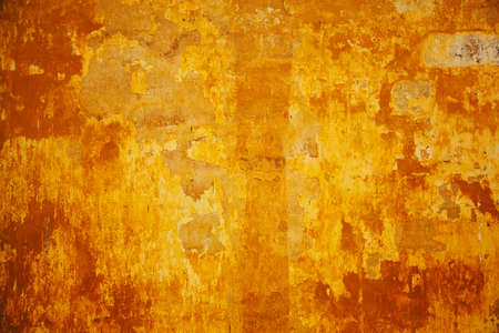Empty space for text or image. The texture of the concrete walls are painted in orange-yellow