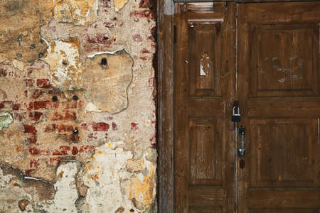 mess: Grunge background - mangy wall with cracks, old wooden door. Textured surface Stock Photo