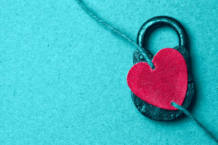 Conceptual photo of red decorative heart and a padlock. Blank space for design