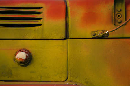 Old truck close-up. Abstract background orange and green colors. Rusty surface in grunge style. Empty space