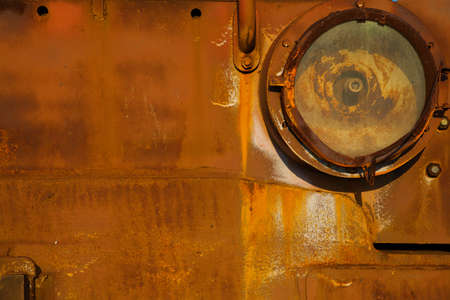 Background, texture, old, iron rusty red surface. The body of old trucks closeup, headlight. Abstract orange rough background in grunge style