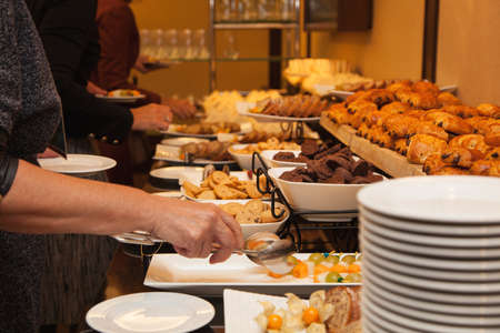 The people at the party eat sweets and cakes. All kinds of snacks. Coffee break with sweet snacks - muffins, cookies, cheesecakes, muffins Stock Photo