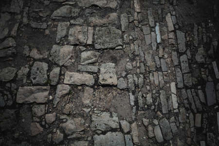 stone pavement. Old road paved with stones. Background, texture of stones and boulders. Dark style Stock Photo