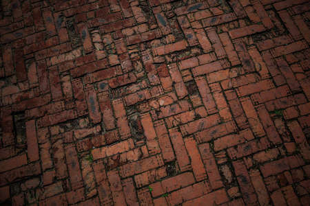 the road is paved with red bricks. Background, texture of the road tiles. Empty space to design. Old vintage style Stock Photo
