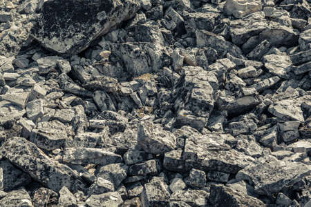 Background, texture of natural stones outdoors. The rocks of the mountains. The texture of the cobblestones. A scattering of rough stones Stock Photo