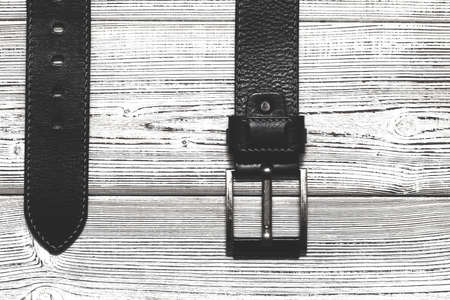 Leather strap with a buckle on a wooden background. The view from the top. Vintage style Stock Photo