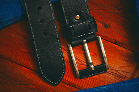 black leather belt with buckle stitched with white thread, close-up top view Stock Photo