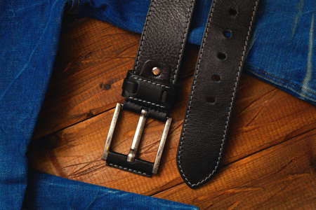 leather belt with buckle and jeans fabric on a wooden background
