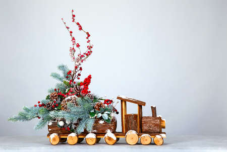 Christmas background. Decorative steam locomotive, decorated with Christmas tree branches, toys and berries. Free space for your text or design Stock Photo