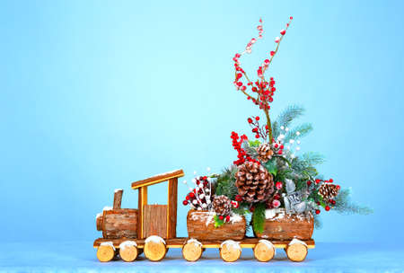 wooden car carrying a Christmas tree and decorations. Space for text.