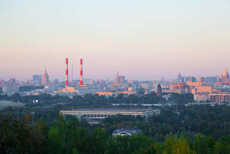 the skyline of a large city at sunset. Residential houses, industrial pipe Фото со стока