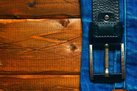 The belt and jeans on a wooden background. Free space for text