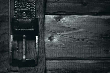 Belt with buckle on wooden background. Background texture of old wooden surface. Free space Stock Photo