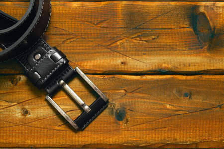 black strap with buckle on the old wooden background. Free space on the background Stock Photo