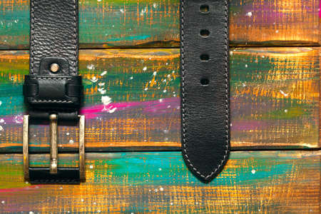 Leather trouser with a buckle on a multicolored wooden background