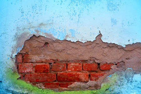 Background texture of old wall with peeling plaster and sticking out of her brick walls. empty space. Place for text Stock Photo