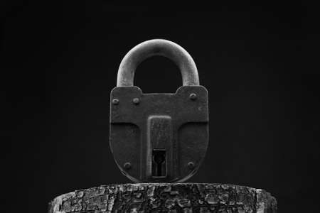 Large old padlock close - up on a black background. Black and white photo 版權商用圖片