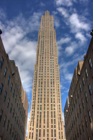 Tall building in New York City with bright blue sky and couds
