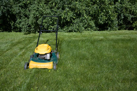 Lawnmower mowing grass with space for copy photo
