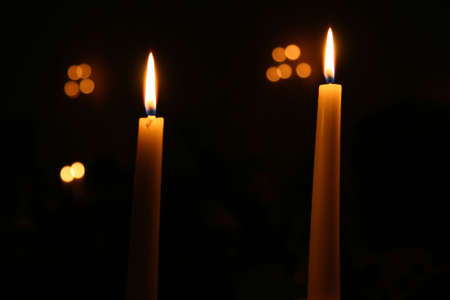 Two Candles burning at night with other lights out of focus in the background