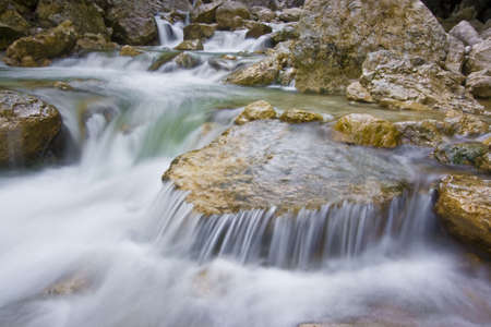 Mountain stream with water flowing over rocks Stock Photo