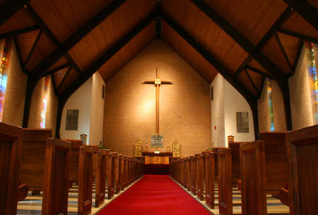 hymn: Inside of a large, modern church with pews and cross visible.