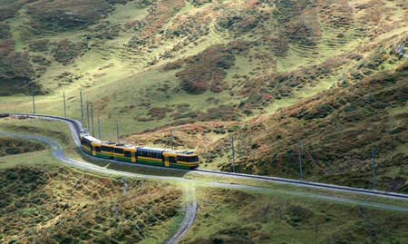 A train traveling up into the mountains.  The track is winding, the light diffused and the vegetation green.