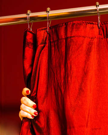 hand held: A portrait photograph of a womans hand with painted finger nails holding a red shower curtain.  The metallic curtain could be held either open or closed by the hand.