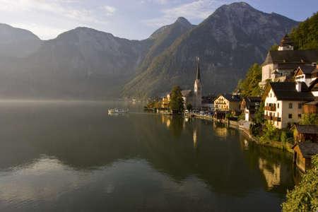 Boat sailing into the morning fog over a lake in Hallstatt, Austria