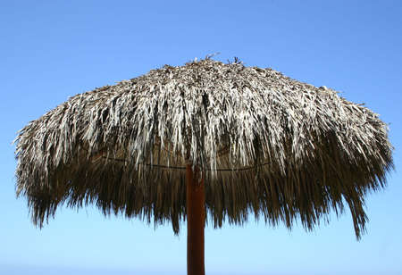 The top of a straw beach umbrella with blue sky in the background  Stock Photo