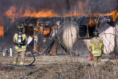 Two firefighters working to put out a fire wihile a home burns Stock Photo