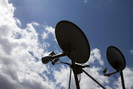 Silhouette of two satellite dish with clouds in the background Stock Photo