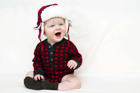 Happy Christmas baby with red plaid shirt, furry, fleece plaid hat with brown boats isolated on white.