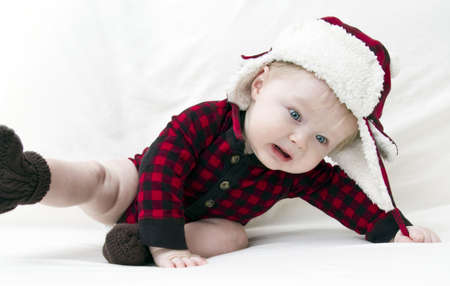Surprised Christmas baby with red plaid shirt and furry wool hat falling over while trying to pull off cap