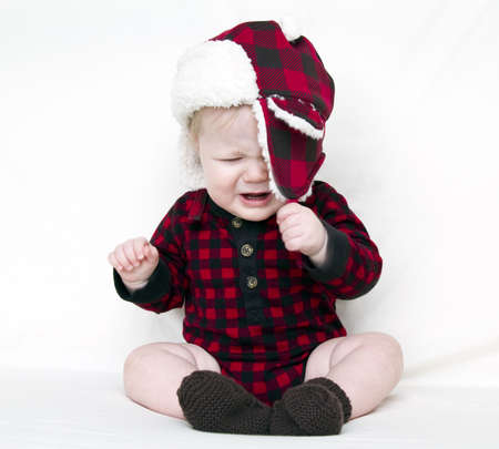 Angry Christmas baby trying to pull off fuzzy hat, with red plaid shirt, isolated on white Stock Photo