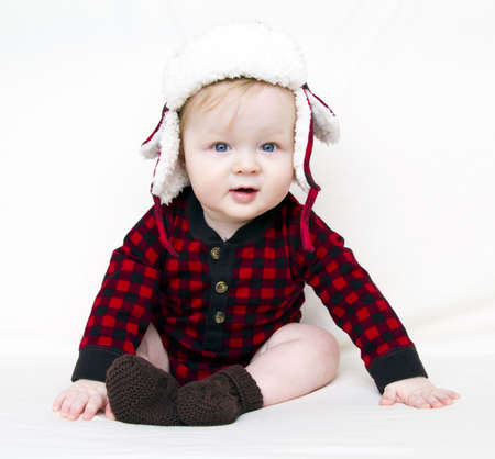 Happy Christmas baby with red plaid shirt, furry, fleece plaid hat with brown boats isolated on white Stock Photo