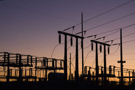 Silhouette of electric power lines and power station at sunset Stock Photo - 7169455