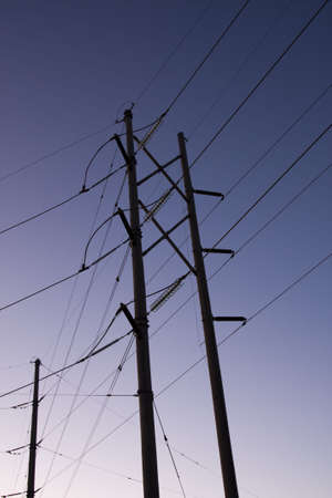 Silhouette of electric power lines and power station at sunset