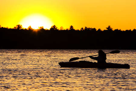 Silhouette of a person kayaking on lake at sunset.  Paddle is in mid-stroke. Stock Photo