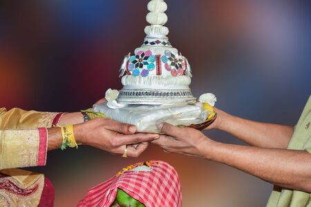The traditional Hindu marriage ceremony of West Bengal in India. Here is the new son-in-law being greeted with a wedding topper. Isolated on multi-colored soft background