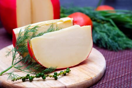 Edam cheese and a piece with fennel and tomatoes on a cutting board 免版税图像