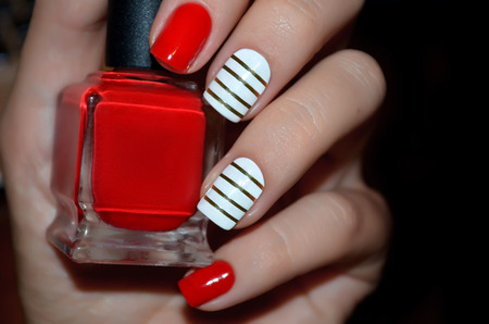 glamour woman: Red and white nail design with red polish bottle. Close up.