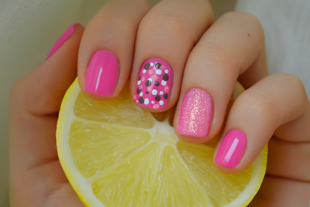 Nict pink nail art with grey and white dots. Photo with lemon 免版税图像
