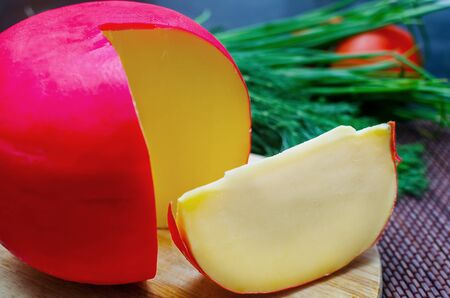 edam: Edam cheese and a piece with fennel and tomatoes on a cutting board Stock Photo