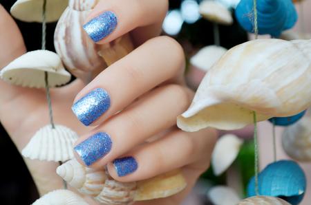 海の貝の背景に美しい青いマニキュアを輝き