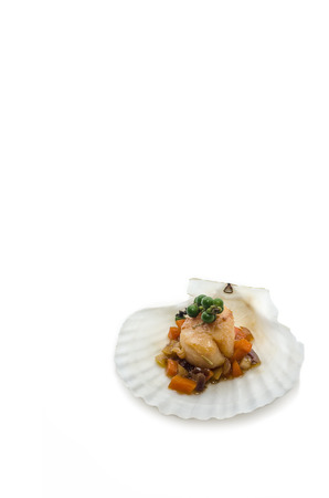 scallop shell: Seared scallops with vegetables, presented on a scallop shell, isolated on white background.