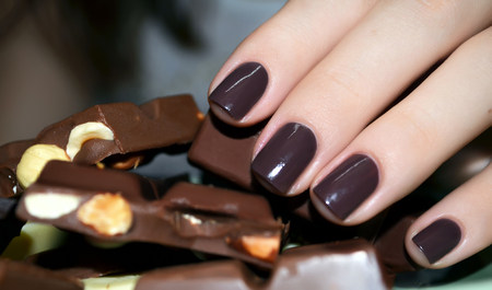 木の葉マニキュアとミルク チョコレートの美しい女性の手
