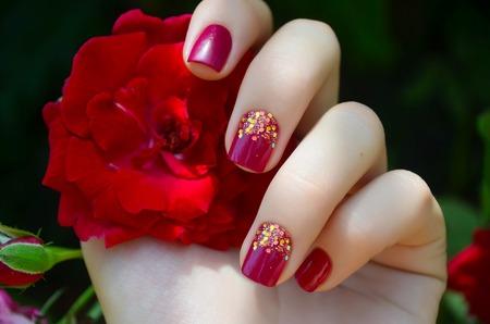 女性の手で輝きピンクのマニキュアと赤い花