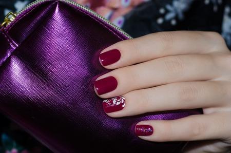 Mão da mulher com escuro design de unhas vermelho e saco roxo para cosméticos